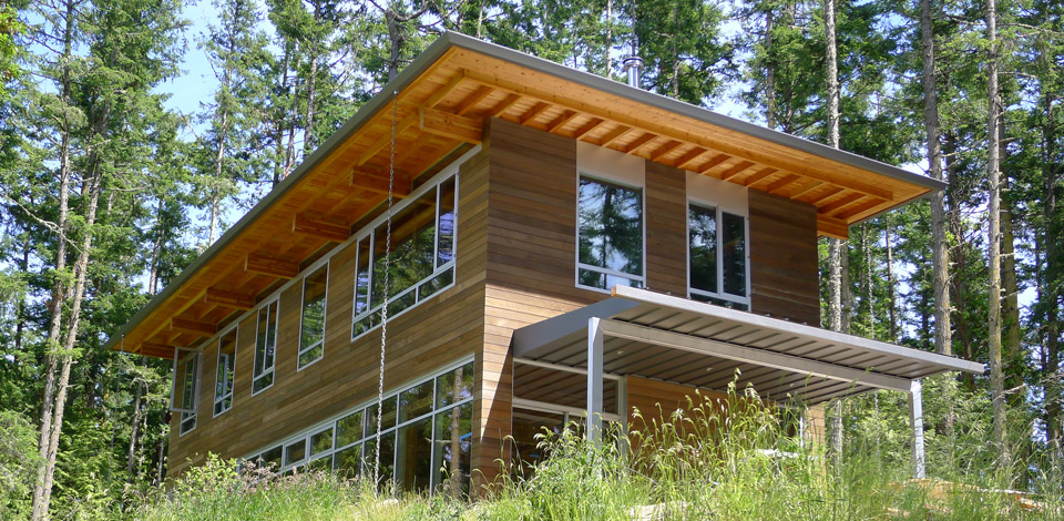 <p>Shaw Island House - San Juan Islands, USA</p><p>A 2,000 sq ft full-time residence based on the Still House system, completed in 2011.</p><p>The elongated layout on two floors was selected to reduce construction costs, and provide a view for almost every room in the house to the pond below and the ocean in the distance to the North. The shallow depth of the plan and abundant windows on the South side allows direct light to penetrate deep into the interior.The post-and-beam construction system permitted continuous windows on the lower level, creating a stong connection with the surrounding forest. This combined with an open floor plan and eleven foot high ceilings creates a spacious interior, while the predominantly wood finishes produces a feeling of sheltered intimacy. Covered Terraces on the South and West sides are flush with the interior floor and extend the conection between the Living level and the landscape. The pre-finished Douglas fir  post-and-beam structure was prefabricated, and assembled on site in eight days, with four framers and a fork lift truck. The purlins, fir decking and roof were also finished at the same time providing a quick umbrella to complete the remainder of the house. The generous overhanging roof on all sides ensures a water tight exterior, and a minimum of exterior maintanence for the cedar siding.<p>