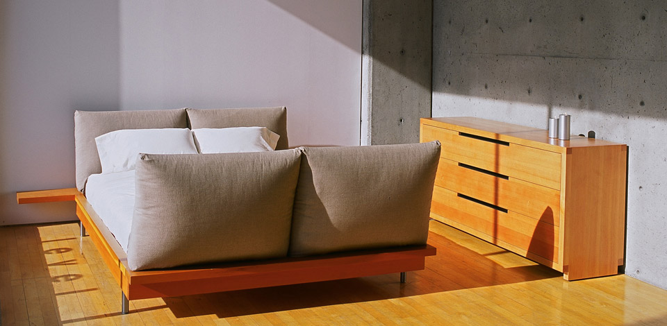 <p>Social Bed</p><p>2002, 2004</p><p>Designed for socializing and sleeping, it consists of a solid wood frame with built-in side tables, suspended wood slats, steel legs, and four headbard and foot board cushions. The Social Bed has been made in all sizes, and a varitey of softwoods, and hardwoods. Intrawest selected 25 king size beds for a development in Whistler in 2004.</p><p>Shown in Queen size with vertical grain Douglas fir.</p><p>Chest</p><p>2004</p><p>Designed as a companion to the Social Bed, Chest is made with solid vertical grain Douglas fir, with Douglas fir veneer ply drawers. The drawer pulls are trimmed with cold-rolled steel bars for durability.</p><p>Height 31'' Width 58'' Depth 19''</p>
